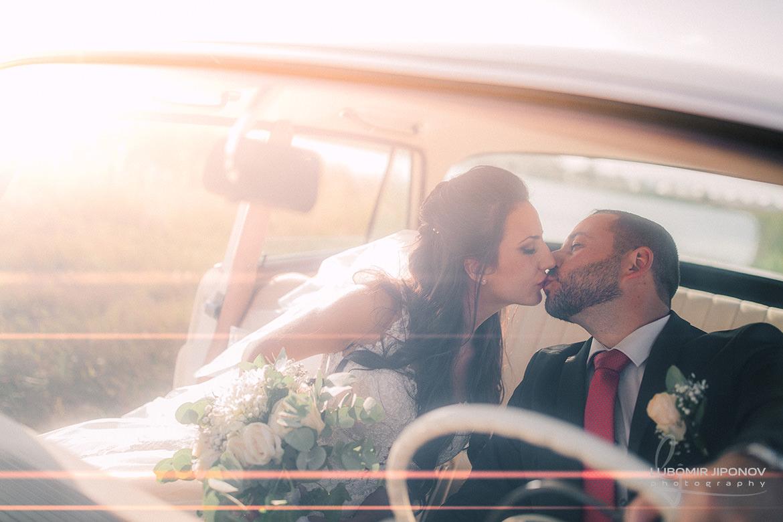 Сватбена фотография на целувка в автомобил с падащи слънчеви лъчи